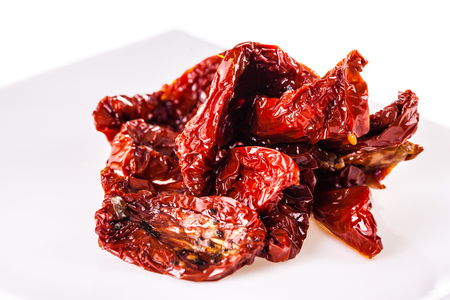 sear: dried tomatoes on a modern plate isolated over a white background