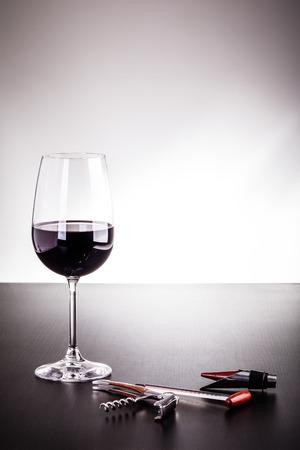 Ein Glas Wein und ein paar Wein Werkzeuge auf einem dunklen Holzoberfläche Standard-Bild - 73191714