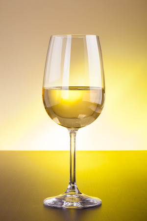 Ein Glas Rotwein auf einer hölzernen Oberfläche gegen einen getönten Hintergrund Standard-Bild - 73341628