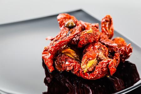 Tomaten auf einem modernen Platte Schuss auf einem schwarzen reflektierende Oberfläche getrocknet Standard-Bild - 73194083