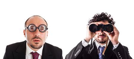 Zwei Geschäftsmann einen mit dicker Brille und eine mit einem Fernglas über einem weißen Hintergrund isoliert Standard-Bild - 73223053