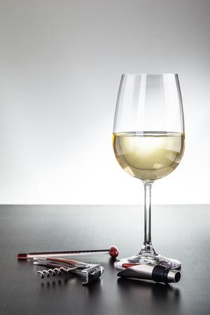 Ein Glas Wein und ein paar Wein Werkzeuge auf einem dunklen Holzoberfläche Standard-Bild - 73198042