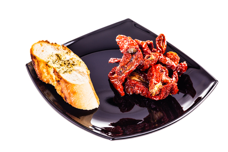 dried tomatoes on a modern plate isolated over a white background