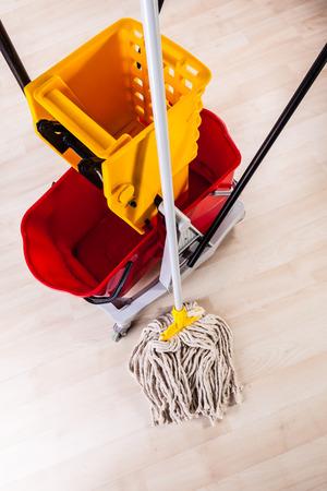 Ein professioneller Moppeimer auf einem hellen Holzboden Standard-Bild - 73194672
