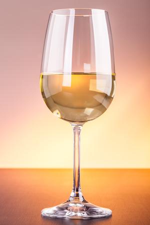 Ein Glas Rotwein auf einer hölzernen Oberfläche gegen einen getönten Hintergrund Standard-Bild - 73519697