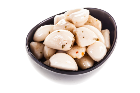 a bowl full of preserved garlic cloves isolated over a white background Banco de Imagens