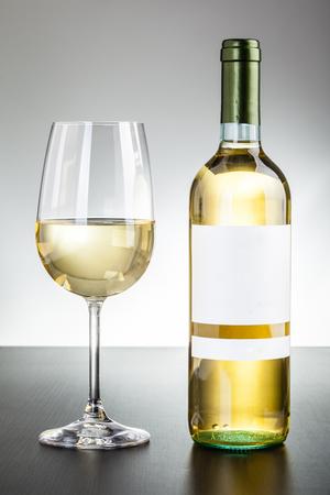 Eine leere etikettierte Flasche Wein und ein Glas Wein auf einem dunklen Holzoberfläche Standard-Bild - 73599434