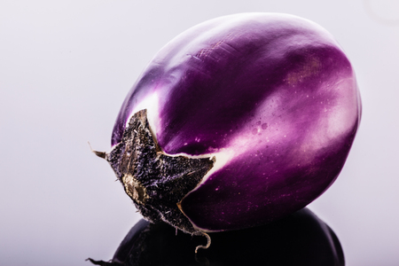 a round italian eggplant variety shot over a black reflective surface