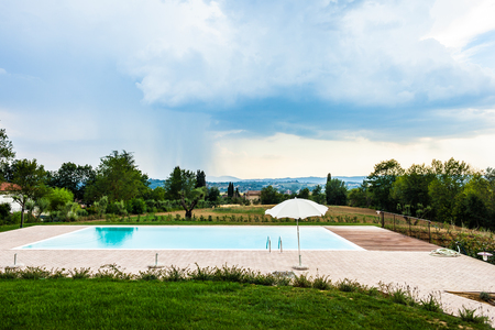a beautiful and luxurious tuscany swimming pool with parasols and chairs Banco de Imagens - 118799598
