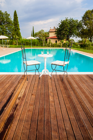 a beautiful and luxurious tuscany swimming pool with parasols and chairs