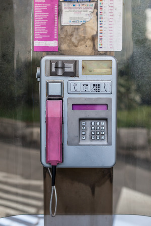 an old phone booth in croatia, with aluminium dial and pink receiver