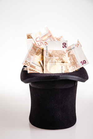 a top hat filled with fifty euro banknotes isolated over a white background Banco de Imagens