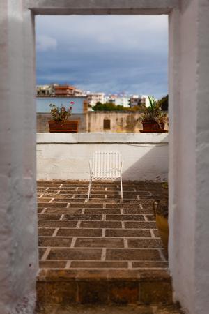 an old white chair at dusk in a mediterranean terrace