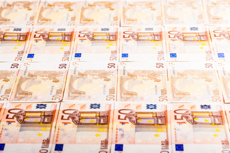a lot of fifty euro banknotes arranged side by side on a flat surface