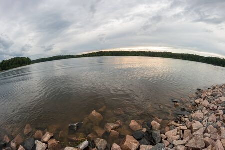 wide  wet: Wide Angle View of Large Lake with Big Storm Clouds at Sunset Stock Photo
