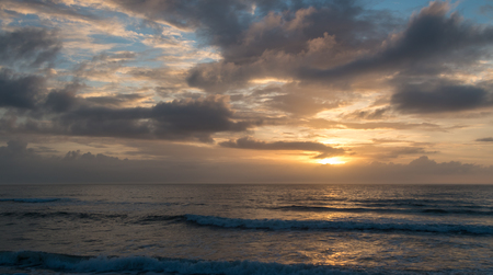 sunrise ocean: Sunrise behind clouds over the beach with ocean waves in the foreground