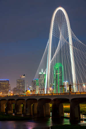 Portrait View of Margaret Hunt Hill Bridge At Night with the US Flag in the background