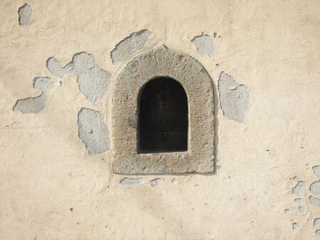 A view of a small window on the wall of old houses in a middleage village in central Italy Stock Photo
