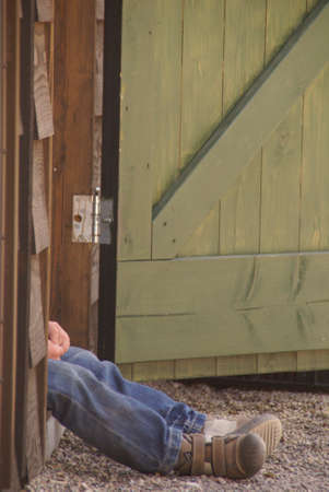 tiring: tired boy with jeans, sitting in the doorway of a barn Stock Photo