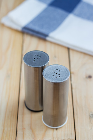Stainless steel salt and pepper shakers on wooden table background