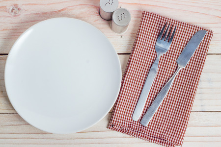 plate setting: Empty white plate and silverware on white wooden table background