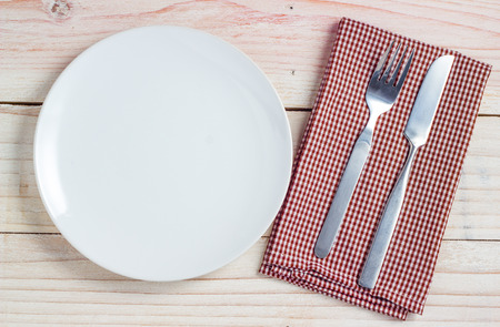 Empty white plate and silverware on white wooden table background