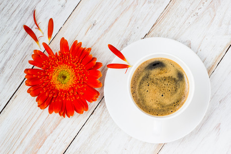 orange colorful gerbera flowers and coffee cup on the wooden table