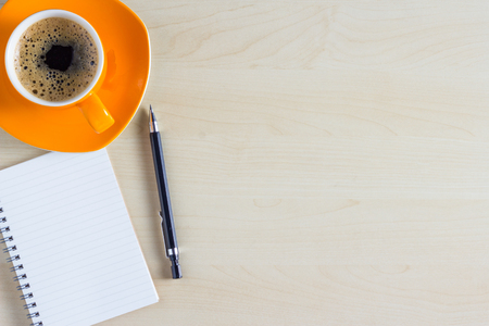 メモ帳とコーヒー カップを持つオフィス テーブル。コピー スペースを上から表示します。