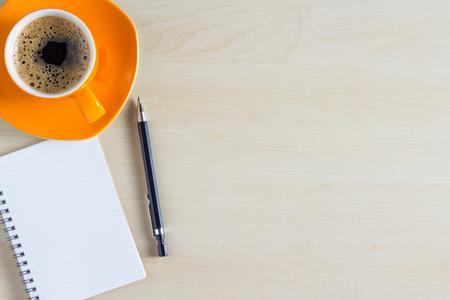Kantoor tafel met kladblok en een koffiekopje. Uitzicht vanaf boven met een kopie ruimte