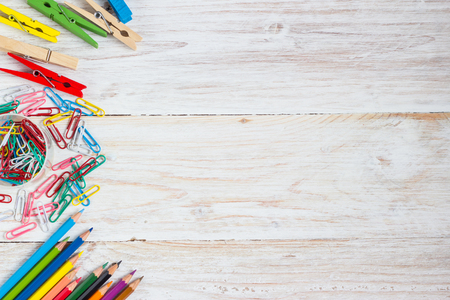 Desk of an artist, colorful pencils  and paperclips on the white wooden table background