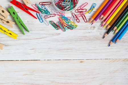 computer graphic: Desk of an artist, colorful pencils  and paperclips on the white wooden table background