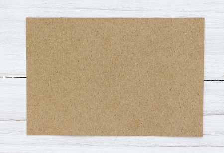 Blank greeting card on wooden table background.