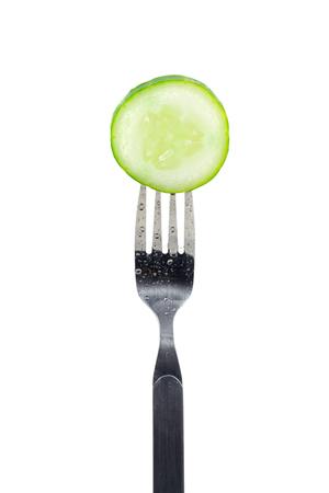Slice of fresh green cucumber on fork isolated on white background. 版權商用圖片