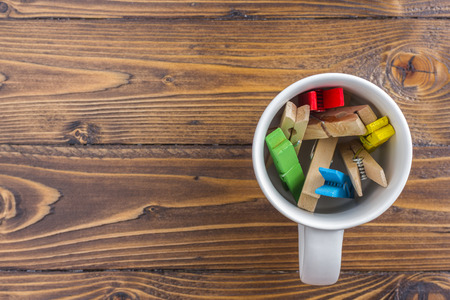 Office table with color paper clips in mug. View from above with copy space