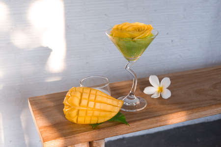 Mango Sticky Rice in martini glass on wooden bench , FamousThai dessert.