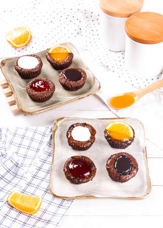 Small Chocolate Cakes with milk ,strawberry ,chocolate and orange sauce on white wooden table background.