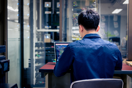 Technicians using laptop while analyzing server in server room,System security specialist working at system controcenter