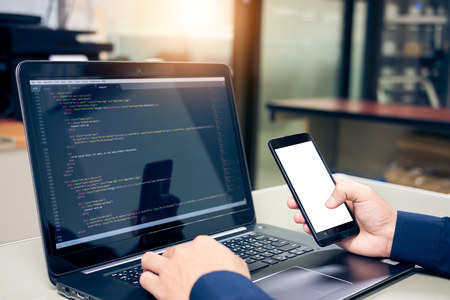 Developing programming and coding technologies on desk, Website design, Programmer working in a software develop company office,Preview code in Smartphone Фото со стока