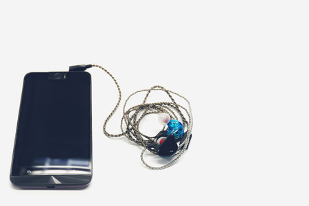Black smartphone and headphone on white background