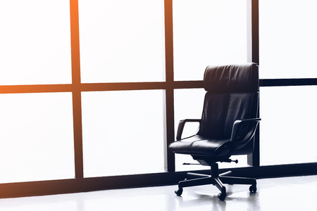 Black executive leather chair in empty office space with large window ,copy space.
