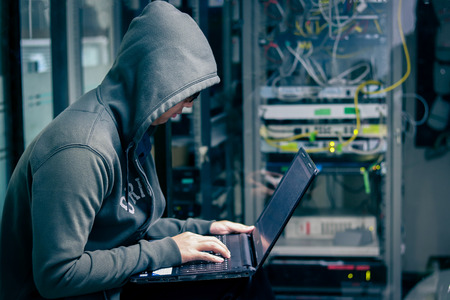 Dangerous Hooded Hacker Breaks into Government Data Servers and Infects Their System with a Virus. His Hideout Place has Dark Atmosphere.