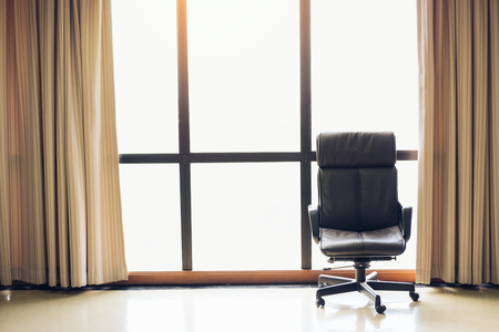 brown executive leather chair in empty office space with large window and drape,copy space.