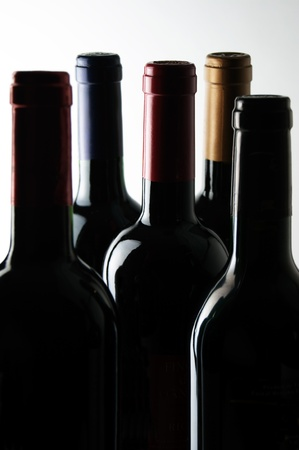 Five bottles of wine in a dark room lit from above. Stock Photo - 10445388