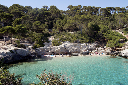 destination scenics: Typical Menorca beach, surrounded by greenery, cliffs and turquoise waters.