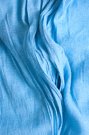 Blue fabric texture with wrinkles and ripples.