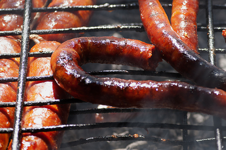 Typical and traditional Spanish barbecue. Sausages are chorizos and chistorra (traditional food of Navarre and Basque Country) on a metal grill. Predominantly red and black.