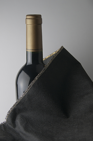 Bottle of red wine with golden cap. The bottle is covered with a black fabric with gold trim