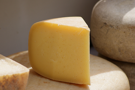 Wedge of idiazabal cheese, illuminated by the sun. Sold in a market of the Basque Country in Spain Stock Photo