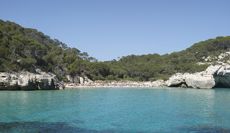 Typical Menorca beach, surrounded by greenery, cliffs and turquoise waters.