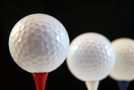 Golf ball on tee, isolated on black photo